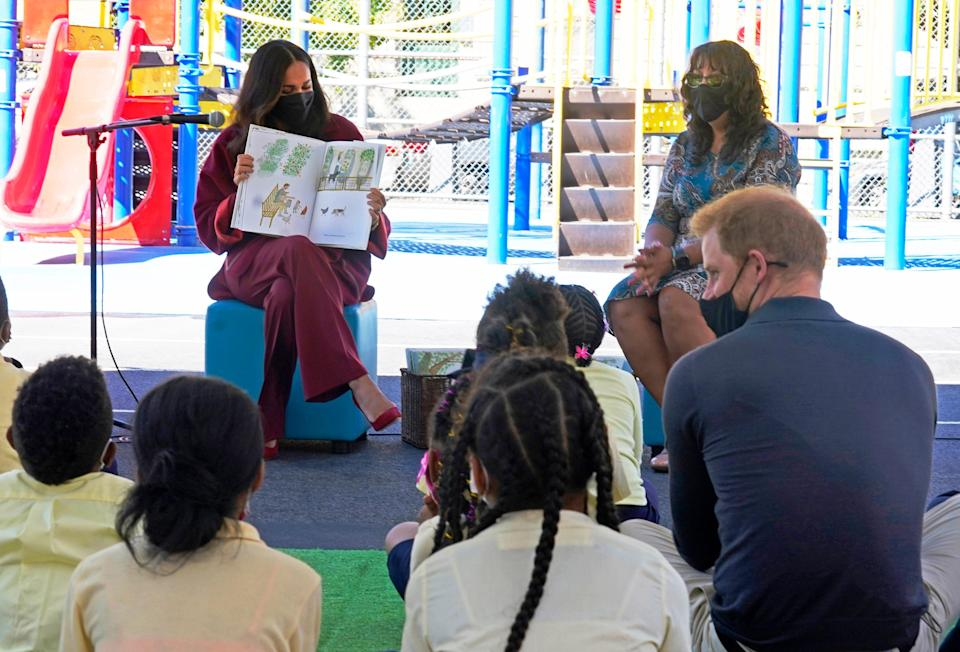 """Duchess Meghan reads from her book """"The Bench,"""" as Prince Harry (bottom right) and second-grade students listen during their visit to P.S. 123, the Mahalia Jackson School, in New York's Harlem neighborhood on Sept. 24, 2021."""