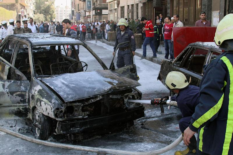 Firefighters extinguish a burning vehicle after two mortar rounds struck the Abu Roumaneh area in Damascus, Syria, Saturday, Oct. 12, 2013. Syria's state news agency said two mortar rounds struck an upscale neighborhood in the Syrian capital of Damascus, killing at least one child and injuring a dozen people. (AP Photo)