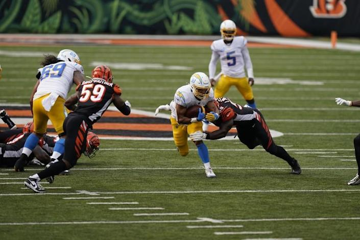 """Chargers' Austin Ekeler is tackled by Cincinnati Bengals' Carl Lawson (58) during the first half Sunday in Cincinnati. <span class=""""copyright"""">(Bryan Woolston / Associated Press)</span>"""