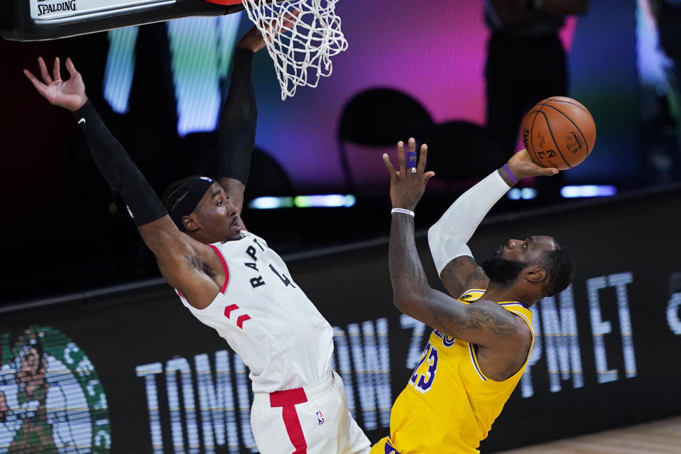 LeBron James (23) de los Lakers de Los Ángeles dispara al aro frente a Rondae Hollis-Jefferson (4) de los Raptors de Toronto, el sábado 1 de agosto de 2020, en Lake Buena Vista, Florida. (AP Foto/Ashley Landis, Pool)