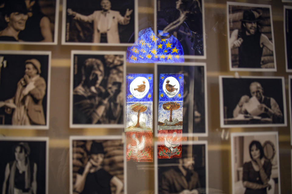 """A painted window is reflected on a billboard displaying photographs of Jewish state Theatre artists during the rehearsals for premiere of the """"The Beautiful Days of My Youth"""" play, based on the diary of Romanian Jewish Holocaust survivor Ana Novac, in Bucharest, Thursday, Oct. 15, 2020. Maia Morgenstern, second from left, head of the Jewish State Theater and a Romanian Jewish actress best known for playing Mary in Mel Gibson's controversial 2004 movie """"The Passion of the Christ,"""" described the play's staging in an interview with The Associated Press as an """"all-feminine project."""" (AP Photo/Andreea Alexandru)"""