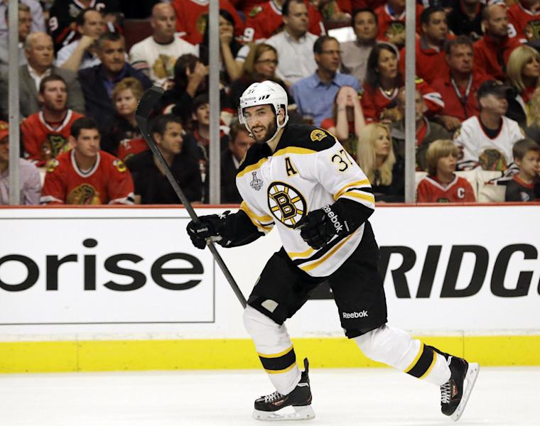 Boston Bruins center Patrice Bergeron (37) celebrates after scoring a goal against the Chicago Blackhawks during the third period of Game 1 in their NHL Stanley Cup Final hockey series on Wednesday, June 12, 2013, in Chicago. (AP Photo/Nam Y. Huh)