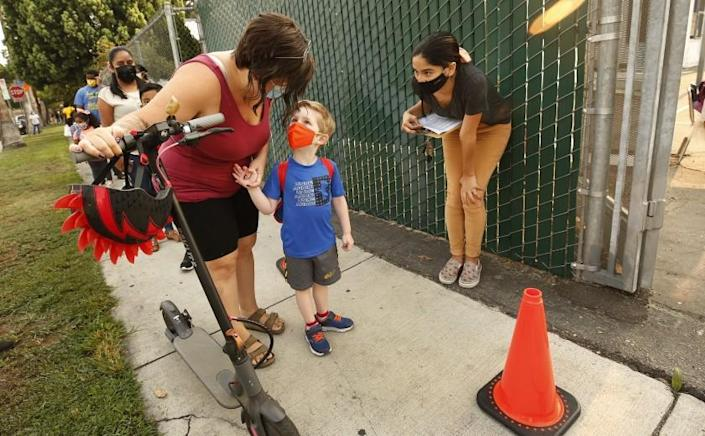"""NORTH HOLLYWOOD, CA - AUGUST 17: Transitional Kindergartner Ryder White with mother Amber White checks in with Yazmin Magallon, Primary Promise Aide at Lankershim Elementary School in North Hollywood as parents and students check for the student name on a list using the Daily Pass website - designed to issue pre-approved health clearances for students to enter campus or present their QR code for entrance to the campus at Lankershim Elementary on Tuesday for the second day of in-class learning for LAUSD schools. """"This is less chaotic today."""" Said Amber. The pre-approved health clearances for students to enter campus appeared to be up and working so the second day of school in the Los Angeles Unified School District appears to be going more smoothly than the first, largely devoid of the long lines and frustrations on back-to-school Monday when the district's student health-check system failed. Lankershim Elementary on Tuesday, Aug. 17, 2021 in North Hollywood, CA. (Al Seib / Los Angeles Times)."""