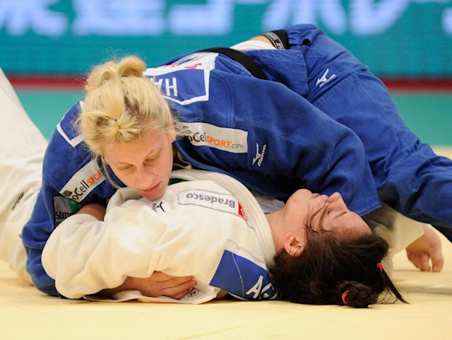 Kayla Harrison (blue jersey) of the US holds Mayra Aguiar (white jersey) of Brazil during their women's over 78kg class semi-final match in the Judo Grand Slam tournament in Tokyo on December 11, 2011. Harrison defeated Aguiar. AFP PHOTO/Toru YAMANAKA (Photo credit should read TORU YAMANAKA/AFP/Getty Images)