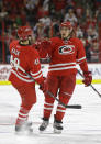 Carolina Hurricanes' Justin Faulk and Victor Rask (49) celebrate Faulk's goal against the Calgary Flames during the second period of an NHL hockey game in Raleigh, N.C., Monday, Nov. 10, 2014. Carolina won 4-1. (AP Photo/Gerry Broome)