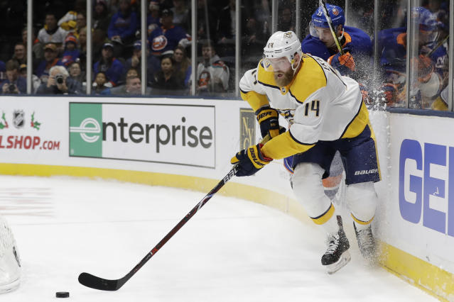 Nashville Predators' Mattias Ekholm (14) fights for control of the puck with New York Islanders' Mathew Barzal (13) during the second period of an NHL hockey game Tuesday, Dec. 17, 2019, in Uniondale, N.Y. (AP Photo/Frank Franklin II)