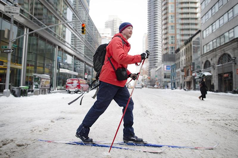 A pedestrian uses his cross-country skis on 58th Street during his morning commute, Friday, Jan. 3, 2014, in New York. New York City public schools were closed Friday after up to 7 inches of snow fell by morning in the first snowstorm of the winter. (AP Photo/John Minchillo)