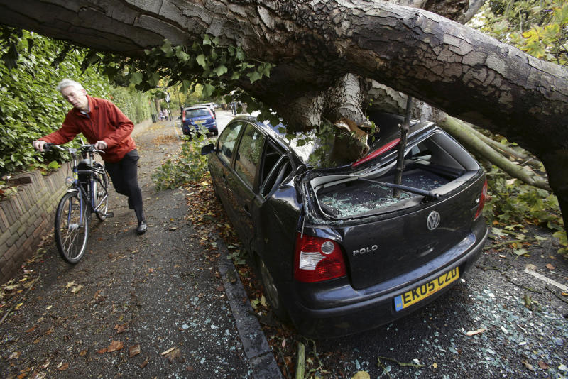 A car is crushed under a fallen tree as a man pushes a bicycle nearby following a storm, in Hornsey, north London, Monday Oct. 28, 2013. A major storm with hurricane-force winds is lashing southern Britain, causing flooding and travel delays including the cancellation of roughly 130 flights at London's Heathrow Airport. (AP Photo/PA, Yui Mok) UNITED KINGDOM OUT, NO SALES , NO ARCHIVES