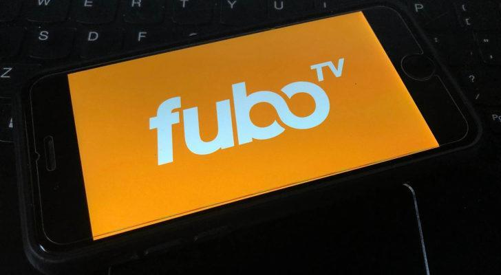 A picture of a FuboTV (FUBO) logo on a smart phone against a computer keyboard.