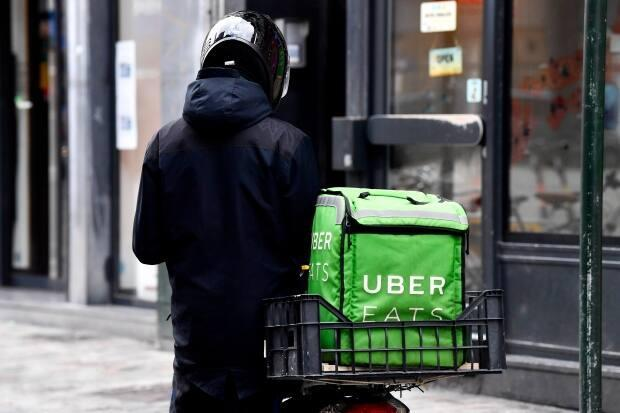 Companies like Uber Eats and other third party delivery apps charge a commission to restaurants which is a percentage of the cost of the customer's order. Quebec is now looking to cap that percentage while dining rooms remain closed in red zones. (Dirk Waem/Belga Mag/AFP via Getty Images - image credit)