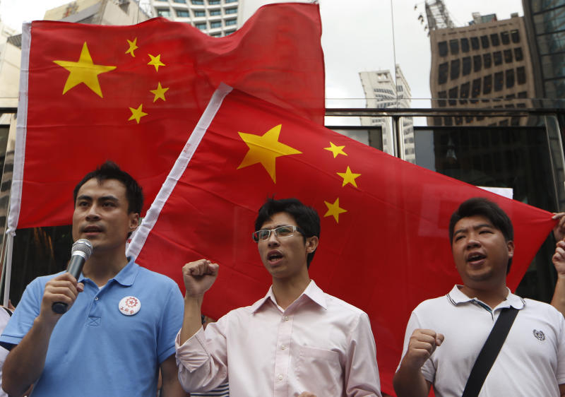 "Anti-Japan protesters shout slogans in front of Chinese national flags during a rally outside the Japanese Consulate General in Hong Kong Thursday Aug. 16, 2012 as they demand Japanese government to release Chinese activists arrested in Japan after landing on Uotsuri Island, one of the islands of Senkaku in Japanese and Diaoyu in Chinese. China's official Xinhua News Agency said the arrests of the 14 people, who included Hong Kong residents and mainland Chinese, had caused tensions over its territorial dispute with Japan to surge ""to a new high."" (AP Photo/Kin Cheung)"