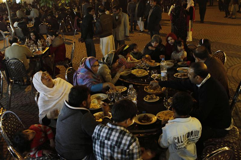 In this Saturday, Jan. 28, 2012 photo, people enjoy traditional sub-continent dishes at Lahore's food park in Pakistan. Archenemies Pakistan and India have competed in a dangerous nuclear arm race, are going head-to-head for the first time in a pair of reality TV shows that pit chefs and musicians from the two countries against each other. (AP Photo/K.M.Chaudary)