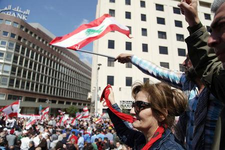 Protesters wave Lebanese national flags during a demonstration against proposed tax increase, in front of the government palace in Beirut