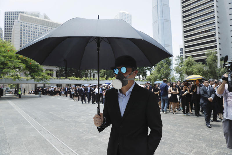 """A man carries an umbrella and wears a face mask as lawyers gather for a protest march in Hong Kong, Wednesday, Aug. 7, 2019. The head of Beijing's Cabinet office responsible for Hong Kong says the territory is facing its """"most severe situation"""" since the handover from British rule in 1997. (AP Photo/Kin Cheung)"""