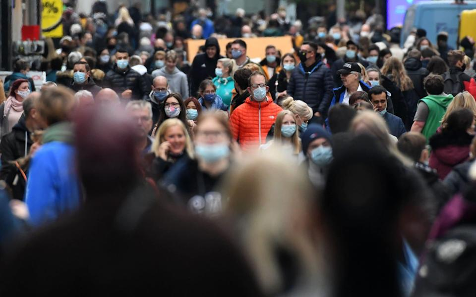 People wearing protective face masks walk in the pedestrian area in the city of Dortmund, western Germany, on October 14, 2020, amid the ongoing novel coronavirus (Covid-19) pandemic. - In Dortmund, wearing a mask is mandatory in the pedestrian zone since October 13 as a measure to curb the spread of the coronavirus. The German Chancellor wants measures toughened up to fight a surge in coronavirus infections, including requiring masks in more places and limiting numbers of people gathering for private events, according to a draft policy paper seen by AFP. The proposals to be discussed with premiers from Germany's 16 states later on October 14 would see the restrictions kick in once an area records 35 new infections per 100,000 people over seven days. (Photo by Ina FASSBENDER / AFP) (Photo by INA FASSBENDER/AFP via Getty Images) - INA FASSBENDER/AFP