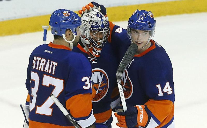 New York Islanders goalie Evgeni Nabokov, center, of Russia, celebrates their 3-0 win against the Detroit Red Wings with Brian Strait (37) and Thomas Hickey (14) in the third period of an NHL hockey game in Detroit, Monday, Dec. 23, 2013. (AP Photo/Paul Sancya)