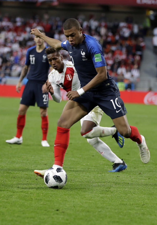 France's Kylian Mbappe, front, is challenged by Peru's Pedro Aquino during the group C match between France and Peru at the 2018 soccer World Cup in the Yekaterinburg Arena in Yekaterinburg, Russia, Thursday, June 21, 2018. (AP Photo/Natacha Pisarenko)