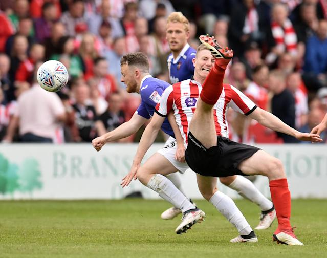 "Soccer Football - League Two Play Off Semi Final First Leg - Lincoln City v Exeter City - Sincil Bank, Lincoln, Britain - May 12, 2018 Lincoln City's Scott Wharton in action with Exeter City's Jake Taylor Action Images/Paul Burrows EDITORIAL USE ONLY. No use with unauthorized audio, video, data, fixture lists, club/league logos or ""live"" services. Online in-match use limited to 75 images, no video emulation. No use in betting, games or single club/league/player publications. Please contact your account representative for further details."