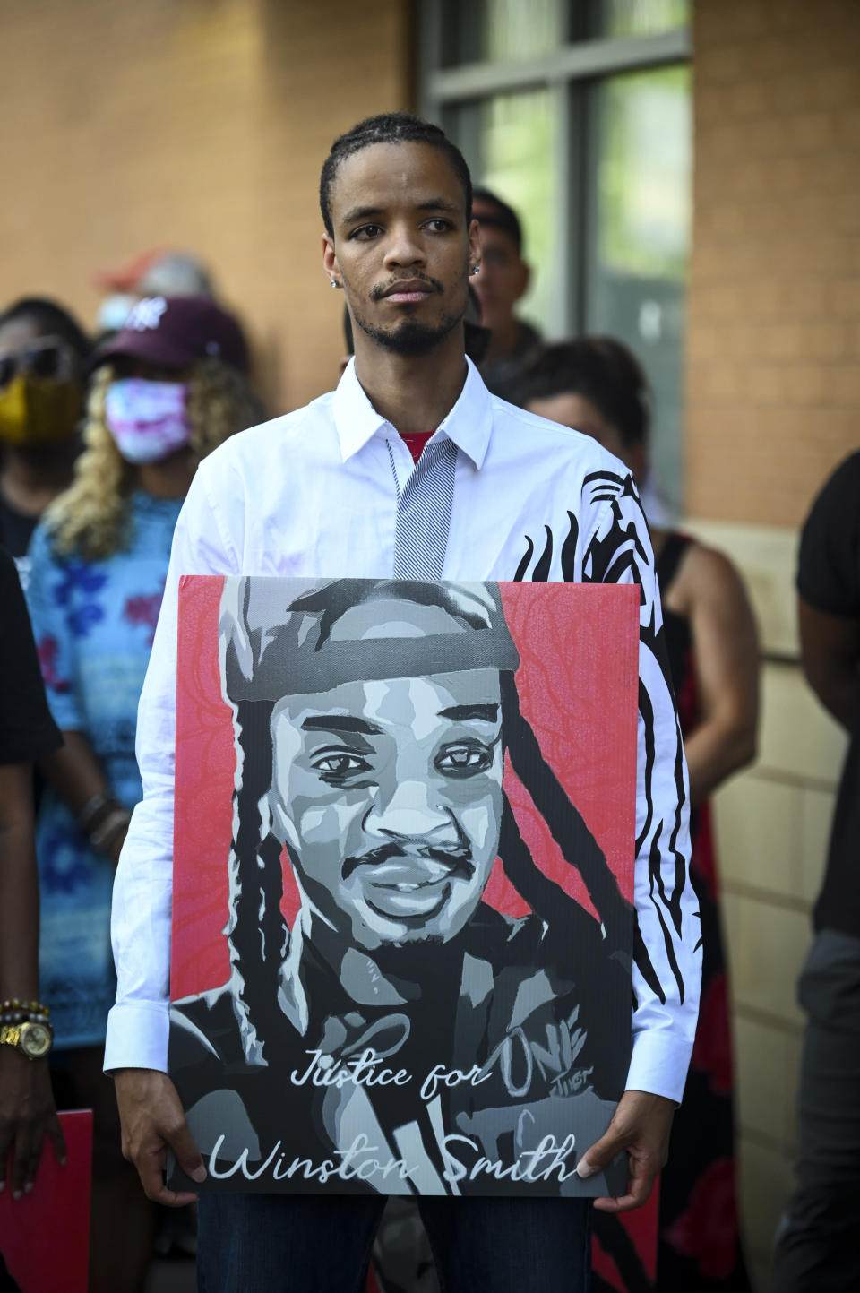 """Kidale Smith, brother of Winston Smith, holds a """"Justice for Winston Smith"""" poster during a press conference Thursday, June 10, 2021 in Minneapolis. Attorneys for the woman in a vehicle when members of a federal U.S. Marshals Service task force fatally shot the driver last week said their client never saw a gun on the man or in the vehicle. (Aaron Lavinsky/Star Tribune via AP)"""