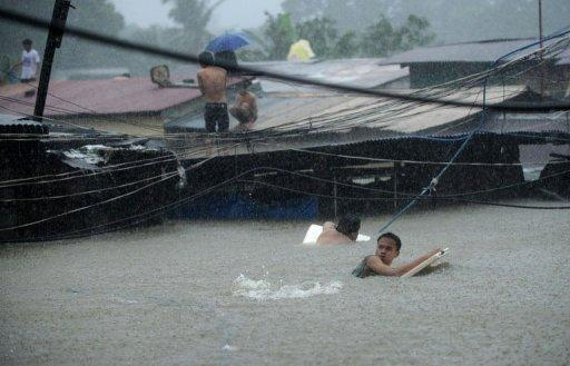 Residents try to cross floodwaters as others wait on the roofs of their houses after a river overflowed in Manila. More than a million people in and around the Philippine capital are battling deadly floods as more monsoon rain fell, with neck-deep waters trapping both slum dwellers and the wealthy on rooftops