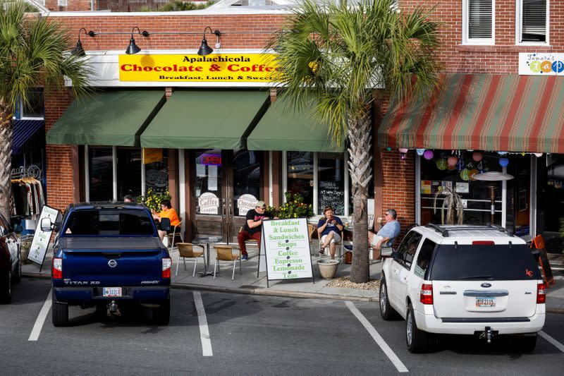 Patrons enjoy the day outside the Apalachicola Chocolate and Coffee Company in Apalachicola, Florida, U.S.