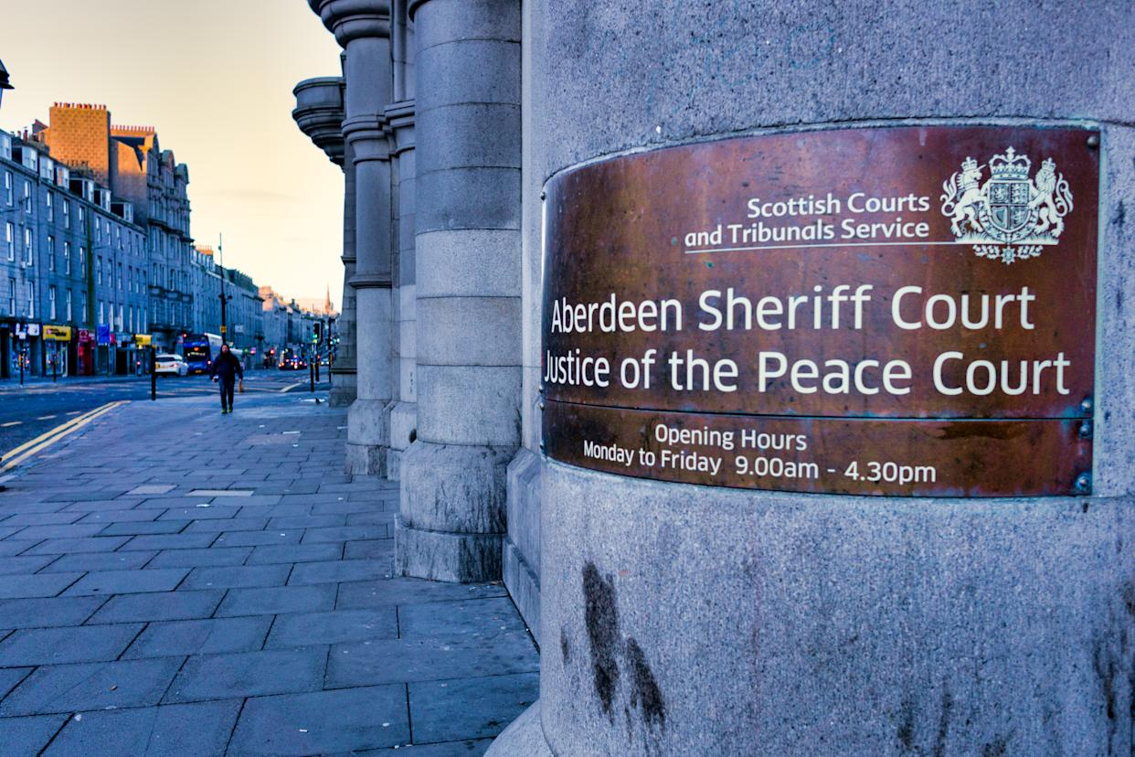 Aberdeen, Scotland, UK - February 10 2019:  Both Aberdeen Sheriff Court and Justice of the Peace Court are governed by the Scottish Courts and Tribunals Service and deal with summary and solemn crime and criminal business.  This is the entrance to this large granite 'grade A' listed building built in the 19th century located on Castle Street, Aberdeen.  It also houses Sheriffs, Sheriff Clerk, the court Social Work Department, Witness Services and the Police cells.
