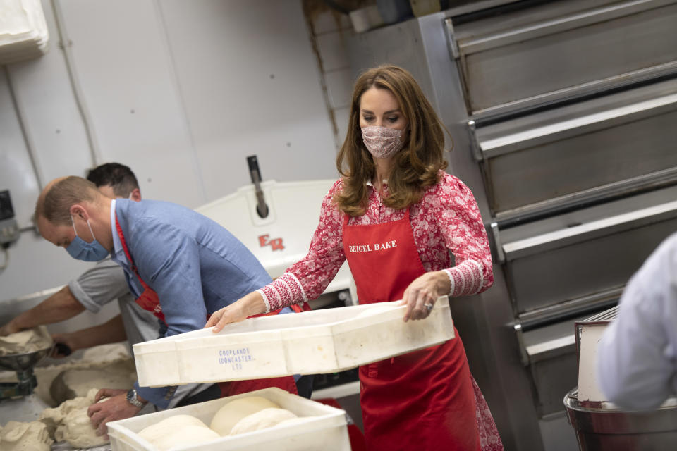 Britain's Prince William, Duke of Cambridge (L) and his wife Britain's Catherine, Duchess of Cambridge help make beigels during a visit to Beigel Bake Brick Lane Bakery in east London on September 15, 2020. - The 24-hour bakery was forced to reduce their opening hours during the pandemic and The Duke and Duchess heard how this affected employees, as well as the ways in which the shop has helped the local community through food donation and delivery. (Photo by JUSTIN TALLIS / POOL / AFP) (Photo by JUSTIN TALLIS/POOL/AFP via Getty Images)