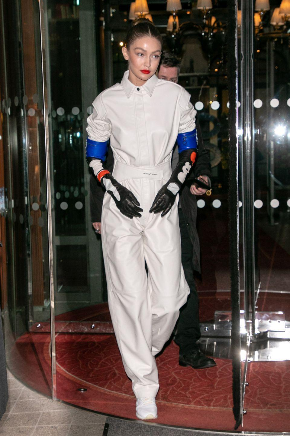 <p>In a white jumpsuit, white sneakers, and multicolor leather gloves. </p>