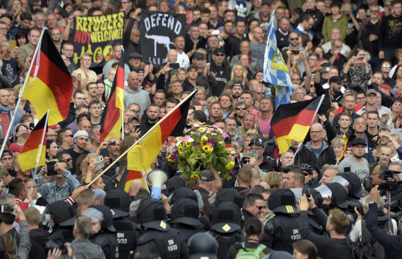 "Protesters carry a wreath as they gather for a far-right protest in Chemnitz, Germany, Monday, Aug. 27, 2018 after a man has died and two others were injured in an altercation between several people of ""various nationalities"" in the eastern German city of Chemnitz on Sunday. (AP Photo/Jens Meyer)"