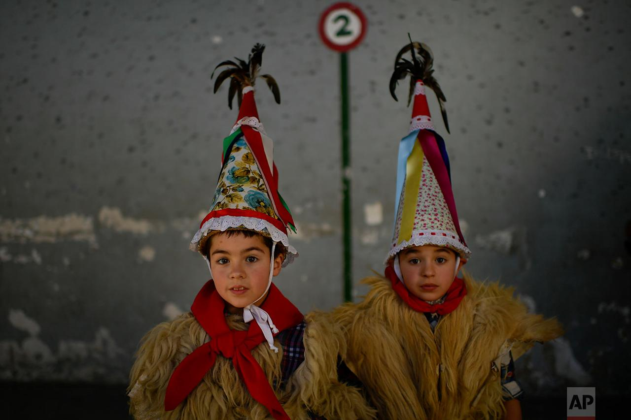 <p>Two young Joaldunaks called Zanpantzar, take part in the Carnival between the Pyrenees villages of Ituren and Zubieta, northern Spain. In one of the most ancient carnivals in Europe, dating from before the Roman empire, companies of Joaldunak (cowbells) made up of residents of two towns, Ituren and Zubieta, parade the streets costumed in sandals, lace petticoats, sheepskins around the waist and shoulders, coloured neckerchiefs, conical caps with ribbons and a hyssop of horsehair in their right hands and cowbells hung across their lower back. (AP Photo/Alvaro Barrientos) </p>