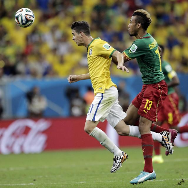 Brazil's Oscar heads the ball away from Cameroon's Maxim Choupo-Moting during the group A World Cup soccer match between Cameroon and Brazil at the Estadio Nacional in Brasilia, Brazil, Monday, June 23, 2014. (AP Photo/Bernat Armangue)