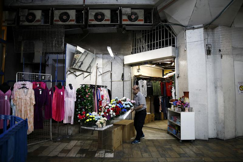 A vendor prepares to open a store at the Central Bus Station on May 29. (Photo: Corinna Kern/Reuters)