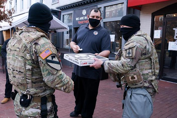 Robert Earley, center, general manager at We The Pizza, hands donated pizza to members of the National Guard from New York, Saturday, Jan. 16, 2021, in Washington, as security is increased ahead of the inauguration of President-elect Joe Biden and Vice President-elect Kamala Harris. (AP Photo/Jacquelyn Martin)