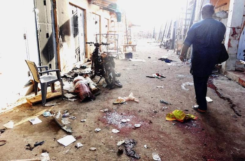 A man walks past blood stains and rubble after twin suicide blasts at Kantin Kwari textile market in the northern Nigerian city of Kano on December 10, 2014 (AFP Photo/Aminu Abubakar)