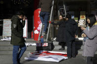 People walk by workers installing Lunar New Year blessing posters outside their retail shop in Beijing, Tuesday, Jan. 15, 2019. China plans to slash taxes, step up spending and provide ample financing to private and small enterprises to help counter the country's worst slowdown since the global financial crisis and the impact of a bruising trade war with the U.S. (AP Photo/Andy Wong)