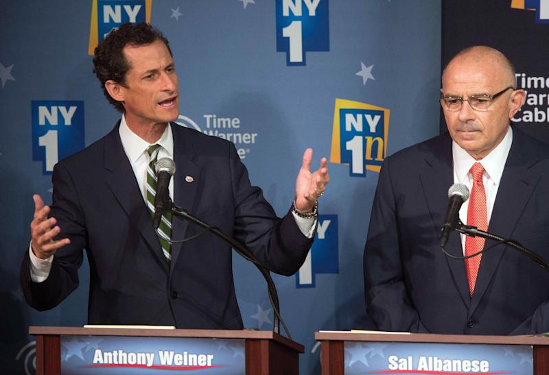 Anthony Weiner, left, gestures while responding to a question, as opponent Sal Albanese listens while the Democratic candidates for Mayor of New York City hold their first debate at the Town Hall, Wednesday, Aug. 21, 2013 in New York. (AP Photo/New York Times, Ruth Fremson, Pool)