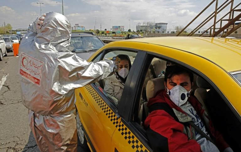 Members of the Iranian Red Crescent test people for coronavirus symptoms (AFP Photo/STR)