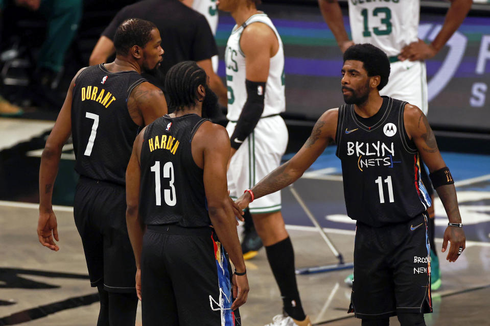 Brooklyn Nets guard James Harden, Kyrie Irving (11) and forward Kevin Durant react after a basket against the Boston Celtics in the first half of Game 5 during an NBA basketball first-round playoff series, Tuesday, June 1, 2021, in New York. (AP Photo/Adam Hunger)