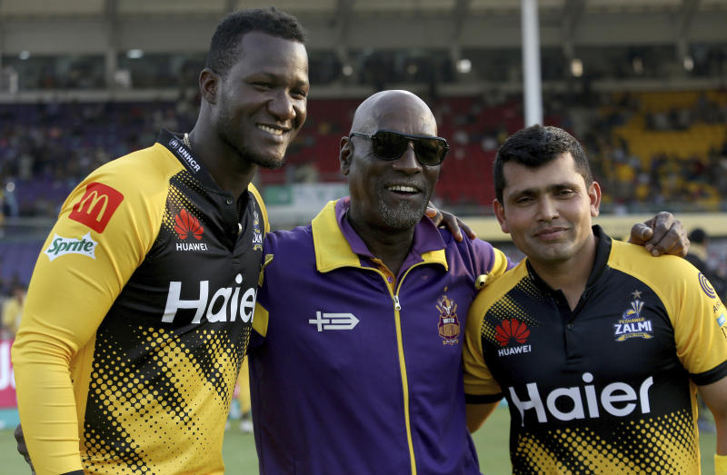 Peshawar Zalmi's players Darren Sammy, left, and Kamran Akmal, right, pose for photographer with former West Indies cricketer Vivian Richards, center, on end of Pakistan Super League T20 cricket match against Quetta Gladiators, in Karachi, Pakistan, Saturday, Feb. 22, 2020. Pakistan is making former West Indies captain Sammy an honorary citizen for his role in restoring international cricket to the country. Pakistan will also give Sammy its highest civilian award - Nishan-e-Pakistan - the Pakistan Cricket Board tweeted Saturday. (AP Photo/Fareed Khan)