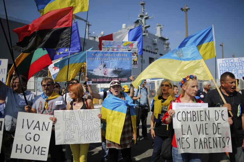 People hold Ukrainian flags and placards during a demonstration against a contract to deliver the Mistral-class helicopter carrier Vladivostok warship to Russia, at the STX Les Chantiers de l'Atlantique shipyard site in Saint-Nazaire