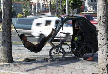 A bicycle cab driver takes a break on a hammock tied to a tree and his bicycle cab along a main street in Manila