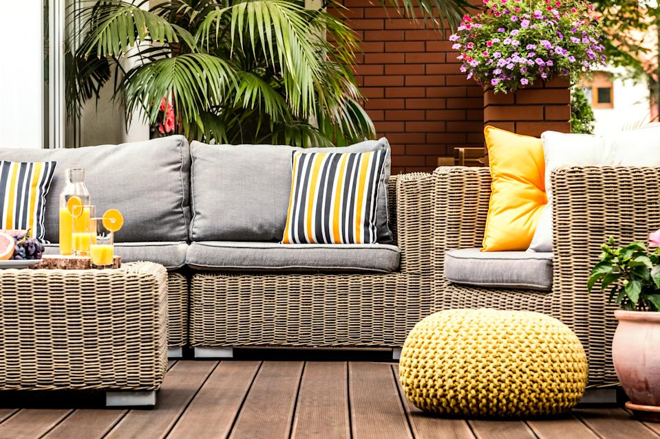 Yellow pouf next to rattan armchair on wooden terrace with striped pillows on sofa