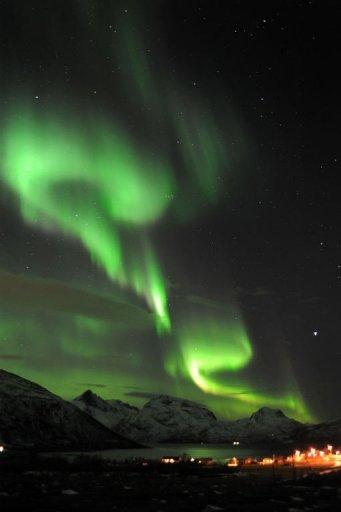 An Aurora borealis is pictured near the city of Tromsoe, northern Norway. Solar radiation from a massive sun storm -- the largest in nearly a decade -- collided with the Earth's atmosphere on Tuesday, prompting an airline to reroute flights and skywatchers to seek out spectacular light displays
