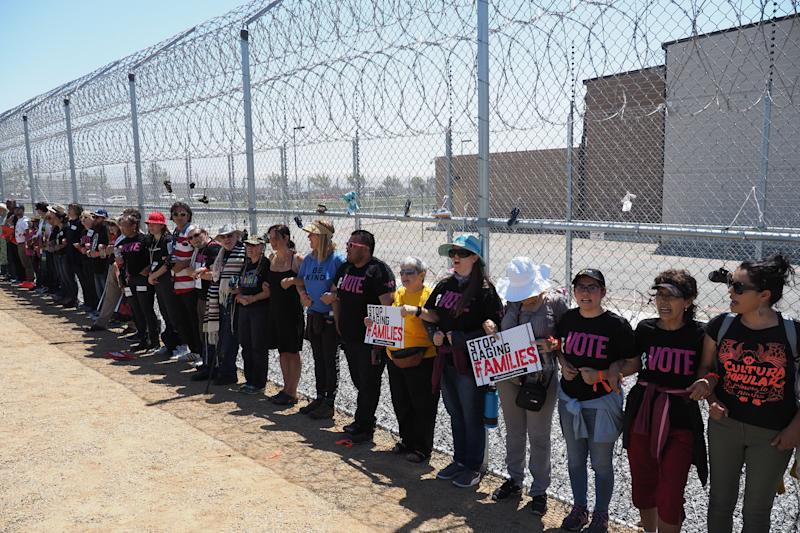 Protestors link arms after tying children's shoes and keys on the fence outside the Otay Mesa Detention Center during a demonstration against US immigration policy that separates children from parents, in San Diego, California June 23, 2018. - The Otay Mesa Detention Center, owned and operated by private prison company CoreCivic, has an inmate population that includes detainees of the U.S. Immigration and Customs Enforcement agency. (Photo by Robyn Beck / AFP) (Photo credit should read ROBYN BECK/AFP/Getty Images)