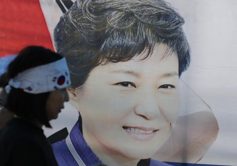 FILE - In this Aug. 29, 2019, file photo, a supporter of former South Korean President Park Geun-hye walks by the banner with her picture near the Supreme Court of Korea in Seoul, South Korea. South Korea's top court upheld 20-year prison term for Park over corruption on Thursday, Jan. 14, 2021. (AP Photo/Lee Jin-man, File)