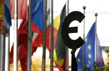 A statue depicting European unity is seen near EU flags outside the European Parliament in Brussels