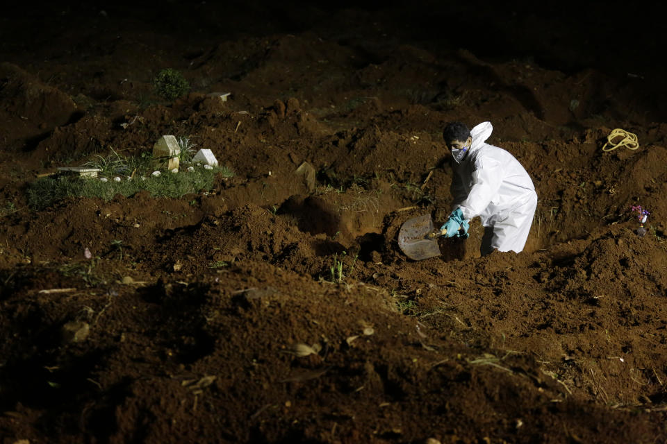 A cemetery worker decked out in protective gear to curb the spread of the new coronavirus, digs a new grave at the Vila Formosa cemetery in Sao Paulo, Brazil, late Wednesday, March 31, 2021. Because of the increased number of deaths in the city, the burial service in some public cemeteries has been extended to the hours of the night. (AP Photo/Nelson Antoine)