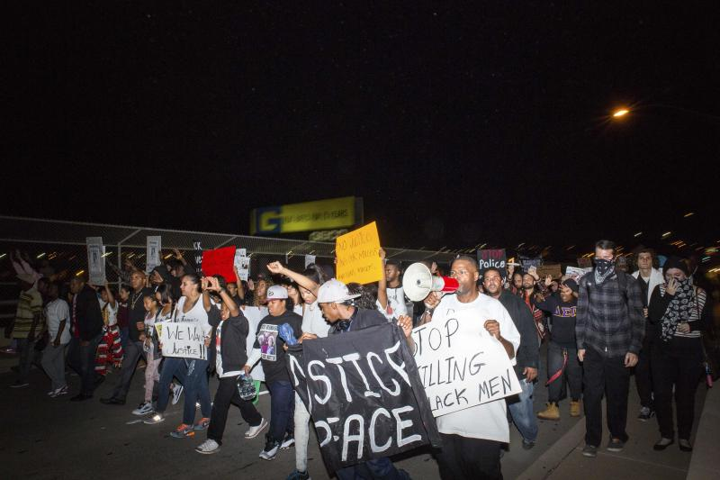 Demonstrators cross the 7th avenue bridge in downtown Phoenix the week after an unarmed man was shot dead by police, in Phoenix, Arizona December 8, 2014. Police say Rumain Brisbon, 34, was killed on December 2 as he struggled with a policeman who suspected he was selling drugs and erroneously believed he felt the handle of a gun in the man's pocket. Brisbon was actually carrying a pill bottle, and an attorney for his mother said accounts from witnesses did not tally with the police version. REUTERS/Deanna Dent  (UNITED STATES - Tags: CRIME LAW CIVIL UNREST)
