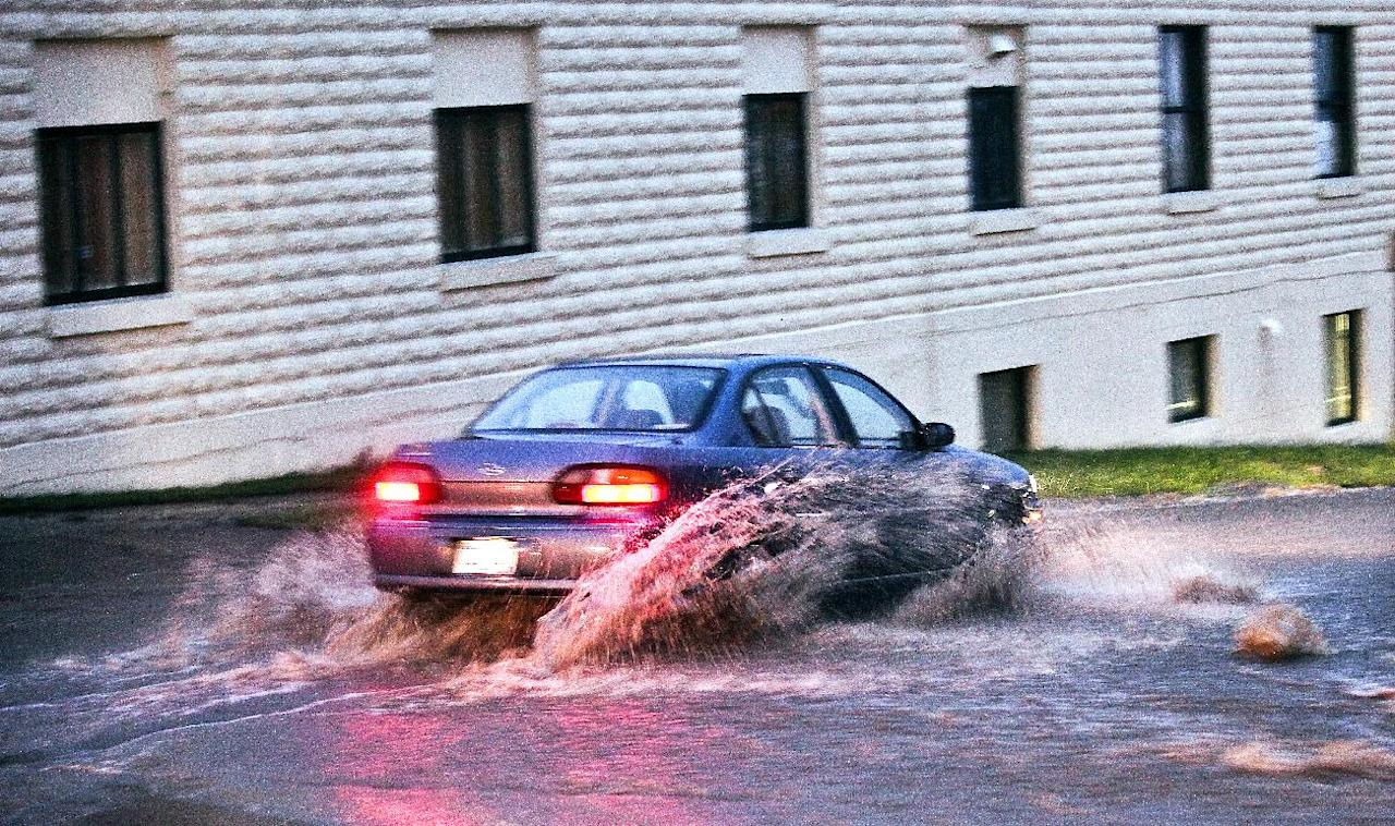 A car navigates high rushing water in Duluth, Minn., Tuesday evening, June 19, 2012, after heavy rains hit the area. Floods fed by a steady torrential downpour forced road closures in northeastern Minnesota on Wednesday, and some people were being urged to evacuate their homes because of the rising St. Louis River. Interstate 35 and downtown tunnels in Duluth were closed and police recommended emergency travel only, warning that numerous sinkholes and washouts were making travel dangerous. (AP Photo/The Duluth News-Tribune, Clint Austin)