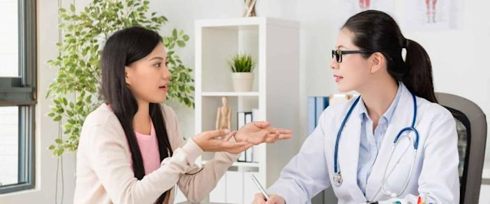 Young woman speaking to doctor, gesturing with her hands.